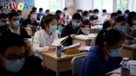 Students wearing face masks are seen inside a classroom during a government-organized media tour at a high school as more students returned to campus following the coronavirus disease outbreak, in Shanghai, China May 7, 2020. (REUTERS/Aly Song)