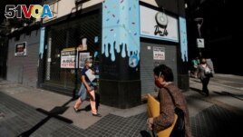 Pedestrians walk past out-of-business stores which display
