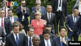 German Chancellor Angela Merkel (C) and U.S. President Barack Obama arrive with other G7 participants for a family picture at the G7 summit at the Elmau castle in Kruen near Garmisch-Partenkirchen, Germany, June 8, 2015.