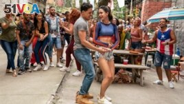This image released by Warner Bros. Picures shows Anthony Ramos, foreground left, and Melissa Barrera in a scene from 'In the Heights.'