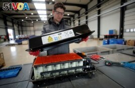 FILE - A used Lithium-ion car battery is opened before its dismantling by an employee of the German recycling firm Accurec in Krefeld, Germany, November 16, 2017. (REUTERS/Wolfgang Rattay/File Photo)