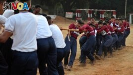 FILE - Indian army women recruits compete with men in a tug-of-war as part of their training before they are inducted as the first women soldiers below officer rank, during a media visit in Bengaluru, India.