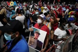 A man holds an image of Cuba's former President and First Secretary of the Communist Party Raul Castro during a rally amid concerns about the spread of the coronavirus disease (COVID-19) in Havana, Cuba, July 17, 2021. REUTERS/Alexandre Meneghini