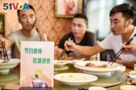 FILE - A sign encouraging people not to waste food is seen at a restaurant in Handan in China's northern Hebei province on August 13, 2020.