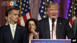 FILE - -In this March 15, 2016 file photo, Donald Trump's campaign manager Corey Lewandowski listens at left as Trump speaks in Palm Beach, Fla.