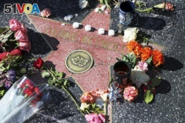 People start a memorial in Los Angeles for Carrie Fisher and Debbie Reynolds.