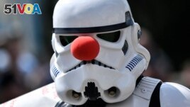 A cosplayer dressed as a Star Wars stormtrooper wears a red nose at a cosplayer meeting in Bottrop, Germany, Saturday, June 15, 2019. (AP Photo/Martin Meissner)