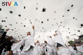 Graduates toss their hats after receiving their diplomas at the graduation and commissioning ceremony for the U.S. Naval Academy's Class of 2021, at the U.S. Naval Academy in Annapolis, Maryland.