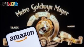 Smartphone with Amazon logo is seen in front of displayed MGM logo in this illustration taken, May 26, 2021. (REUTERS/Dado Ruvic/Illustration)