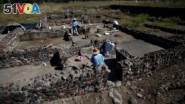 Men work at one of the multi-family apartment compounds at La Ventilla, one of the most extensively excavated neighborhoods in the ancient city of Teotihuacan, in San Juan Teotihuacan, on the outskirts of Mexico City, Mexico November 7, 2019. (REUTERS/Gustavo Graf )