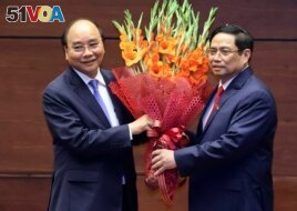 Vietnamese newly elected President Nguyen Xuan Phuc, left, and newly elected Prime Minister Pham Minh Chinh pose for a photo in the National Assembly in Hanoi, Vietnam on Monday, April 5, 2021. (Hoang Thong Nhat/VNA via AP)