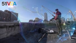 Kurth Reis is seen through a giant bubble he made on a rooftop in San Francisco, California. He makes bubbles by dipping his long sticks connected by small ropes into a mixture. (REUTERS/Nathan Frandino)