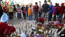 People pray at a memorial to honor the victims of Wednesday's shooting attack, Dec. 5, 2015, in San Bernardino, Calif.