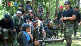FILE - In this undated file photo, Abu Sayyaf spokesman Abu Sabaya, right foreground, stands with militants in Basilan, the Philippines.
