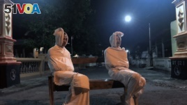 Volunteers Deri Setyawan, 25, and Septian Febriyanto, 26, sit on a bench as they play the role of 'pocong', or known as 'shroud ghost', to make people stay at home amid the spread of coronavirus disease (COVID-19), outside the gate of Kepuh village in Suk
