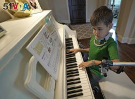 Braden Scott uses a device to support his left arm as he practices on the piano in Tomball, Texas on Friday, March 29, 2019. Braden was diagnosed with the syndrome called acute flaccid myelitis, or AFM, in 2016.