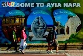 Tourists walk at southeast resort of Ayia Napa, in the eastern Mediterranean island of Cyprus, Saturday, May 22, 2021. (AP Photo/Petros Karadjias)