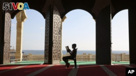A Palestinian youth reads verses of the Quran, Islam's holy book, during the holy Islamic month of Ramadan at the beach side Mosque in Gaza City, June 9, 2016. (AP Photo/Adel Hana)