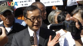 Opposition leader of Cambodia National Rescue Party Sam Rainsy, center, delivers a speech during a gathering to mark Human Rights Day, in front of National Assembly, in Phnom Penh, Cambodia, Wednesday, Dec. 10, 2014. (AP Photo/Heng Sinith)