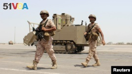 FILE - Soldiers from the United Arab Emirates walk past a military vehicle at the airport of Yemen's southern port city of Aden, Aug. 12, 2015.