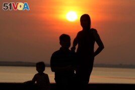 A family takes a photo as the sun rises in Phnom Penh, Cambodia, Friday, Jan. 24, 2020. ((AP Photo/Heng Sinith))