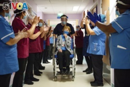 Margaret Keenan, 90, is applauded by staff as she returns to her ward after becoming the first patient in the UK to receive the Pfizer-BioNTech COVID-19 vaccine, at University Hospital, Coventry, England.