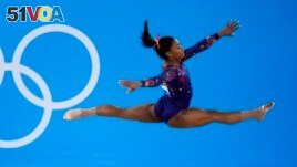 FILE- Simone Biles, of United States, performs her floor exercise routine during the women's artistic gymnastic qualifications at the 2020 Summer Olympics, Sunday, July 25, 2021, in Tokyo. (AP Photo/Ashley Landis)