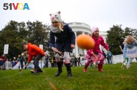 FILE - Julia Stimson, 8, from Alexandria, Va., and other children participate in the annual White House Easter Egg Roll on the South Lawn of the White House in Washington, Monday, April 2, 2018. (AP Photo/Pablo Martinez Monsivais)