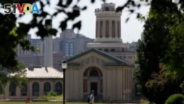FILE - In this file photo from June 7, 2019, a man walks by Hamerschlag Hall on the Carnegie Mellon University in Pittsburgh. Colleges in the U.S. saw a drop among international students in the fall of 2020. (AP Photo/Gene J. Puskar, File)