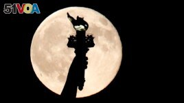 In this July 31, 2015, file photo, a full moon rises behind the torch of the Statue of Liberty as seen from Liberty State Park in Jersey City, N.J. But what does it mean