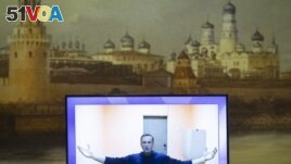 Russian opposition leader Alexei Navalny appears on a TV screen during a live session with the court during a hearing of his appeal in a court in Moscow, Russia, Thursday, Jan. 28, 2021, with an image of the Moscow Kremlin in the background.