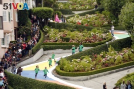 FILE - In this Aug. 19, 2009 file photo, children run down Lombard Street in San Francisco, transformed for the day into a gigantic Candy Land board game to commemorate the game's 60th anniversary. Tourists may soon have to pay a fee to drive down the street.