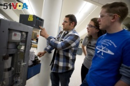 Andrew Brunn (left), a civil engineering major, works with a measurement device in the Northeastern University Civil Engineering Lab as civil engineering majors Sarah Thomas (center) and Peter Calves (right) look on.