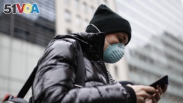 In this file photo, a pedestrian uses her phone while wearing a face mask in Herald Square, Thursday, March 12, 2020, in New York. (AP Photo/John Minchillo)