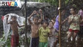 Filipino children watch as arrested drug suspects, not shown, wait outside an alleged drug den following a raid where two suspects were killed and about 90 people arrested during operations as part of the continuing