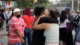 Women hug while waiting for some information about their relatives who are inmates at Litoral Penitentiary, after a prison riot, in Guayaquil, Ecuador, Wednesday, September 29, 2021. (AP Photo/Angel DeJesus)