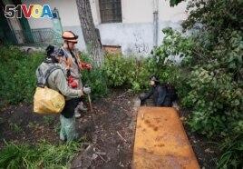 Diggers Andriy Ryshtun and Oleksandr Ivanov and historian Hanna Tychka prepare to go underground to explore the city sewage system. REUTERS/Gleb Garanich