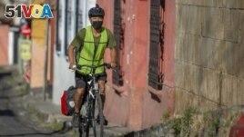 Bonifaz Diaz rides through the streets of Quetzaltenango, Guatemala, Saturday, Jan. 30, 2021. (Henning Sac via AP)
