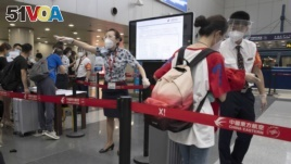 FILE - Airline employees redirect a traveler at a checkpoint for passengers from high-risk areas to present their COVID-19 test results before checking in for their flight at the Beijing Capital Airport terminal 2 in Beijing on Wednesday, June 17, 2020.