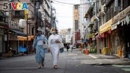 FILE - Women wear kimonos in the street at the Senso-ji temple area in Tokyo, Japan, August 18, 2021. (REUTERS/Molly Darlington)