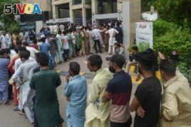 People queue up and wait to get themselves inoculated with the Covid-19 coronavirus vaccine at a vaccination centre in Karachi on August 1, 2021. (Photo by Rizwan TABASSUM / AFP)