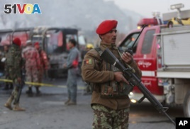An Afghan soldier stands guard by a damaged bus at the site of a suicide attack by the Taliban in Kabul, Afghanistan, December 2014. Officials warn of similar violence this week and have alerted U.S. citizens in Afghanistan. (AP Photo/Rahmat Gul)