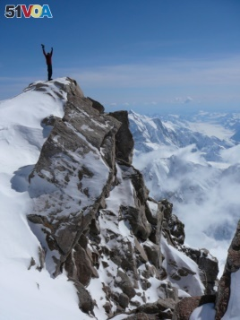 A mountaineer stands atop a tall peak in Denali National Park