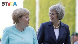 German Chancellor Angela Merkel, left, and British Prime Minister Theresa May walk on the red carpet during a military welcoming ceremony at the chancellery in Berlin Wednesday, July 20, 2016, on May's first foreign trip after being named British Prime Mi