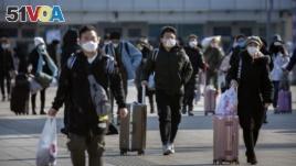 Travelers wear face masks as they walk outside the Beijing Railway Station in Beijing, Saturday, Feb. 15, 2020. (AP Photo/Mark Schiefelbein)