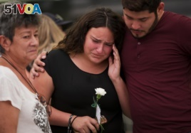 Glorymar Valley, center, is comforted by Christian Caballero, right, and Natividad Rivera, as they mourn the loss of their friend Javier Jorge-Reyes
