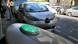 An electric car is being charged in a Paris street, France, Sept. 12, 2017.