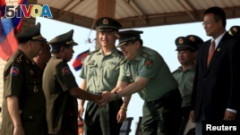 In this March 2015 file photo, Cambodian Defense Minister Tea Banh, second left, shakes hands with a Chinese army adviser during a graduation ceremony at the Army Institute in Kampong Speu province. (REUTERS/Samrang Pring)