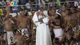 A priest holds a baby as clergy and indigenous people wait for the arrival of Pope Francis in Puerto Maldonado, Madre de Dios province, Peru.
