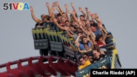 People ride a roller coaster at Worlds of Fun amusement park Saturday, June 2013, in Kansas City, Missouri. (AP Photo/Charlie Riedel)